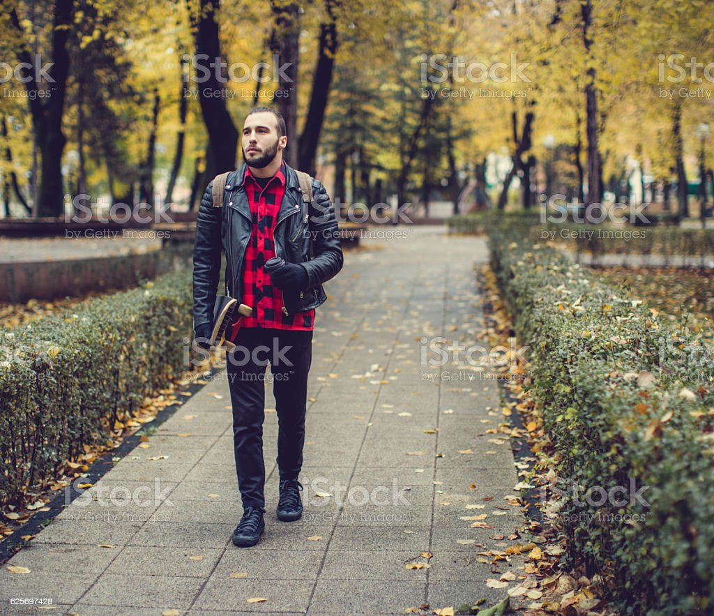 Walking with skateboard and coffee stock photo