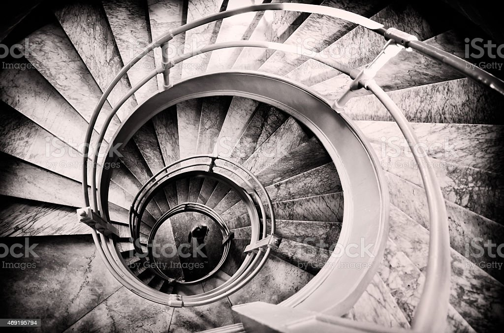 Walking woman in center of spiral stairs stock photo