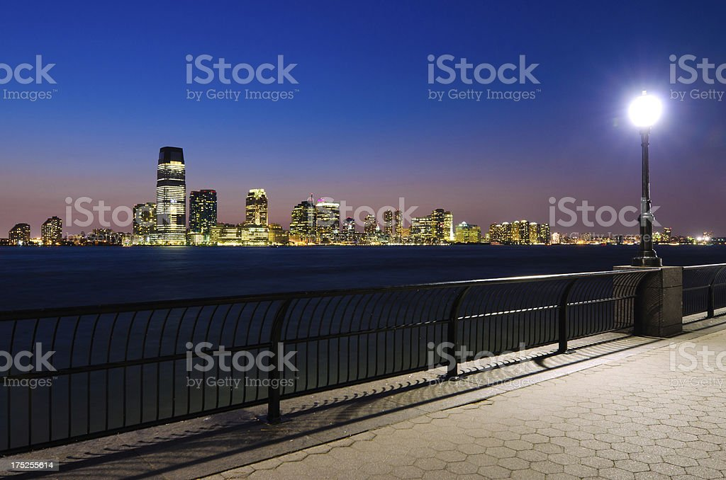 Walkway along water in Lower Manhattan with Jersey City skyline royalty-free stock photo