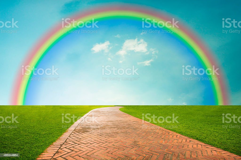 Walkway between green fields and rainbow in blue sky background royalty-free stock photo