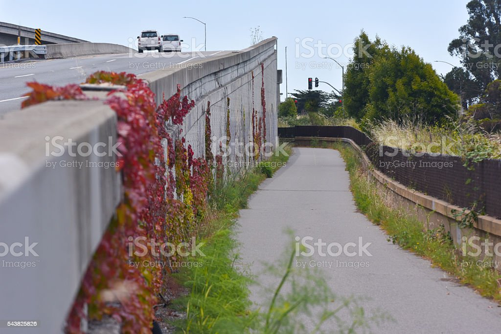 Walkway next to a freeway with fence stock photo