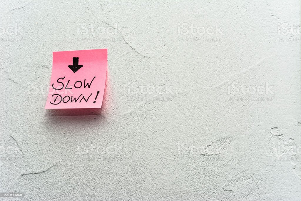 Wall, adhesive note slow down and arrow stock photo
