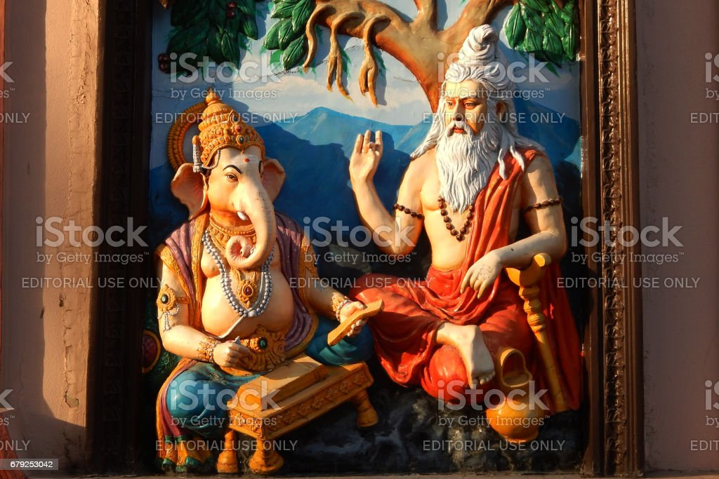 Wall art of Sage Vyasa dictating the story to help God Ganesha to write Hindu epic Mahabharata stock photo