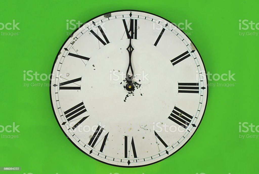 Wall clock at 12 o'clock isolated on green background stock photo