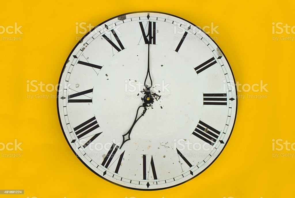 Wall clock in front of a yellow background stock photo