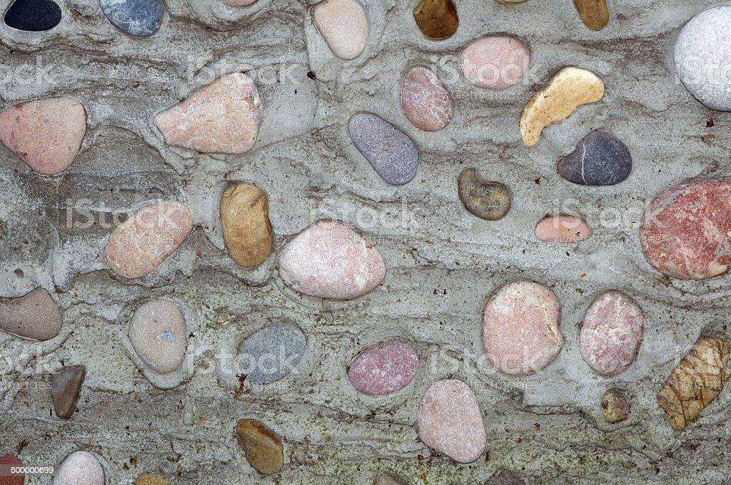 Wall from old stones in concrete stock photo