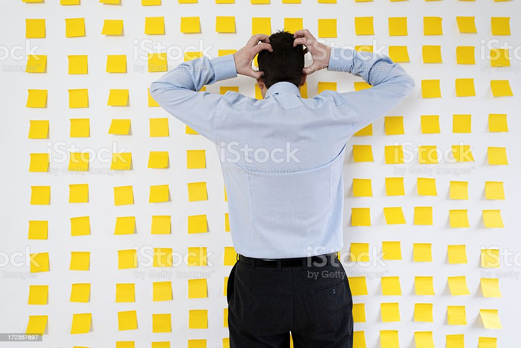 Wall full of post it notes and a desperate man stock photo