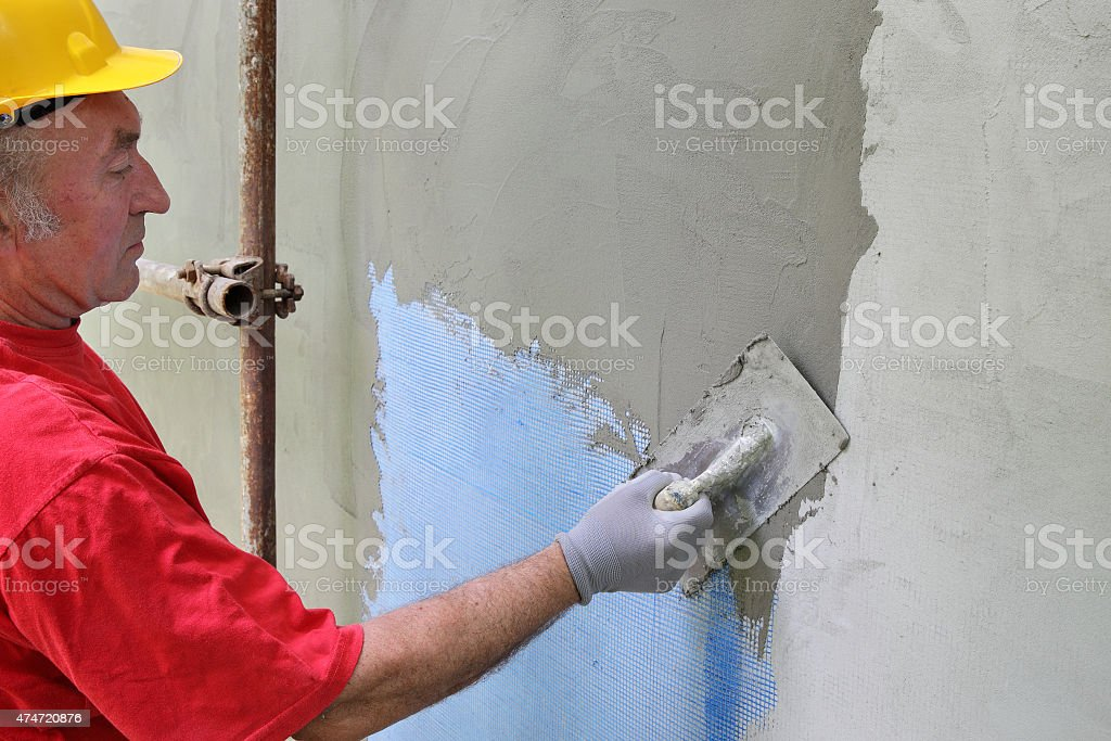 Wall insulation, spreading mortar over mesh stock photo