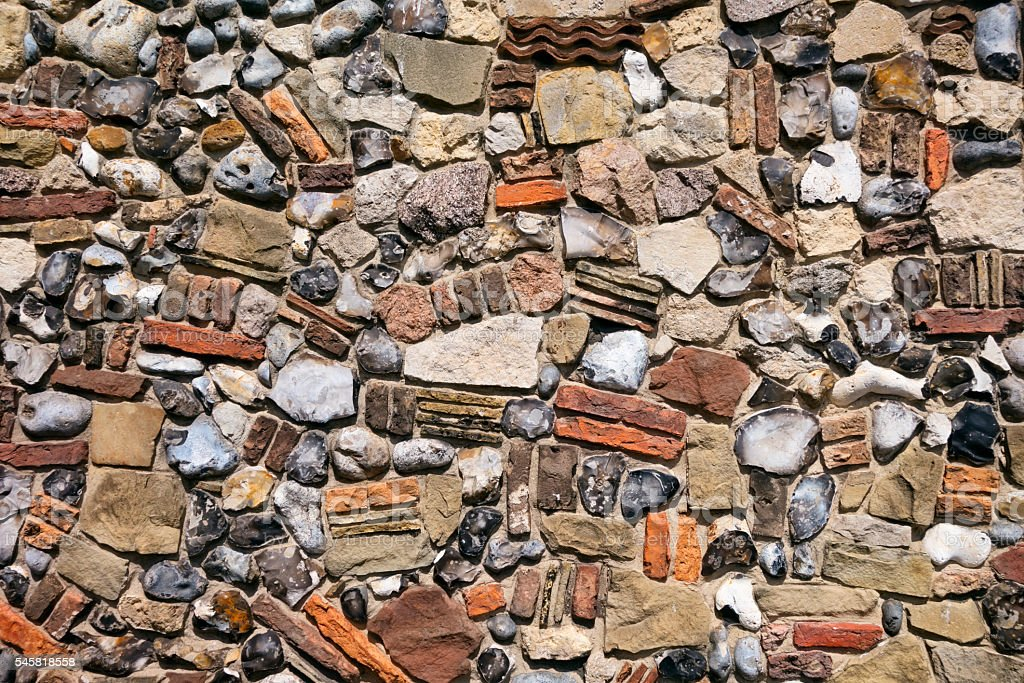 Wall made of brick, tiles and mixed stone stock photo