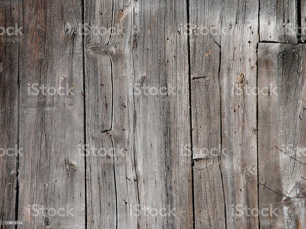 Wall of a wooden barn with cracks and knots in the wood stock photo
