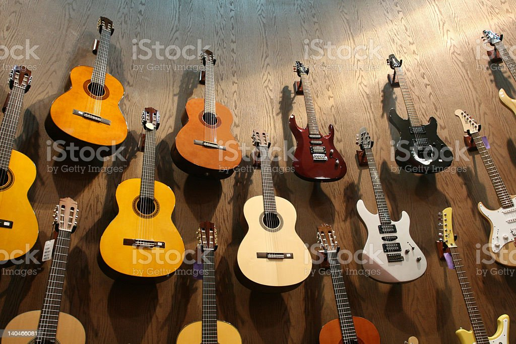 A wall of acoustic, classical, and electric guitars stock photo