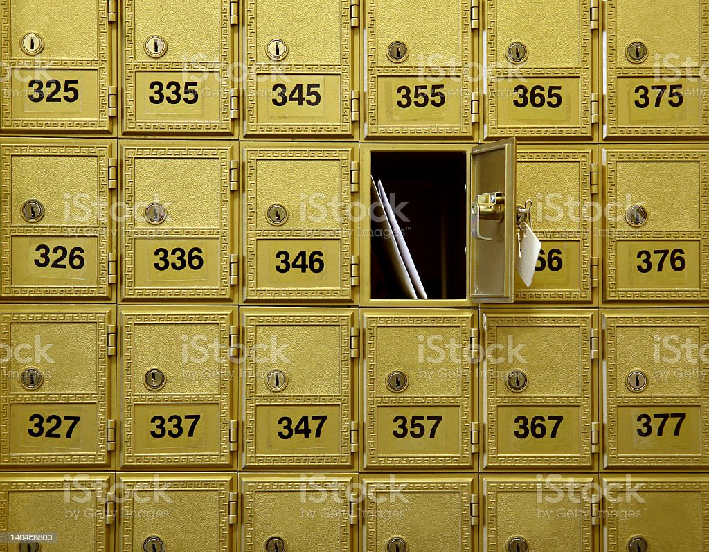 A wall of mailboxes with one open stock photo