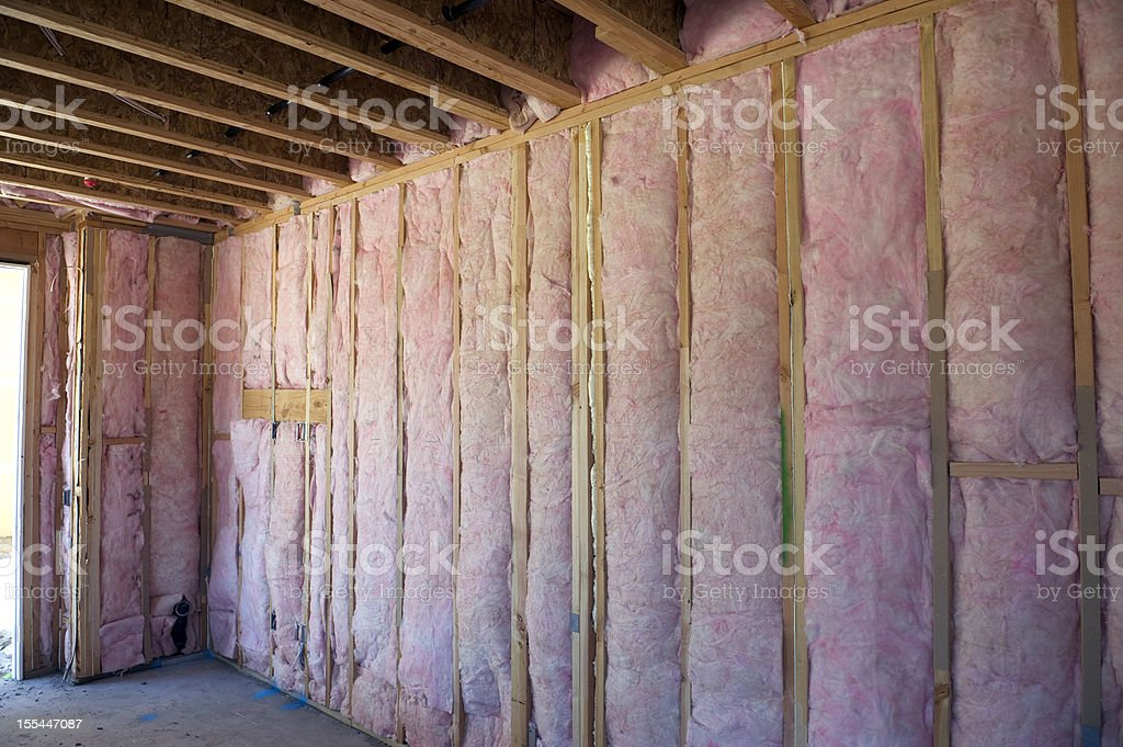 Wall of pink insulation in house stock photo