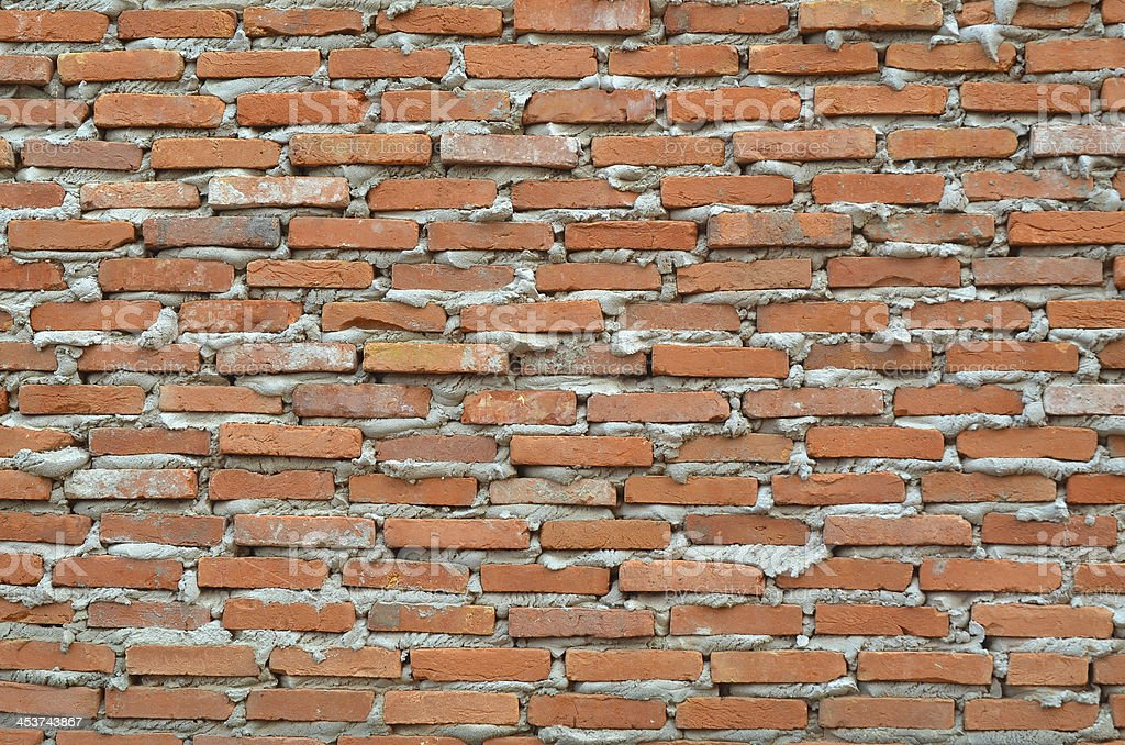Wall of red brown clay bricks with overflowed cement. stock photo