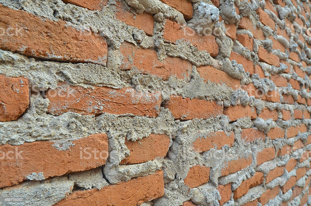 Wall of red brown clay bricks with overflowed cement stock photo
