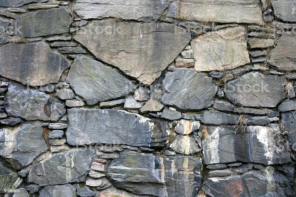 Wall of stacked gray stone with river rocks and slate royalty-free stock photo