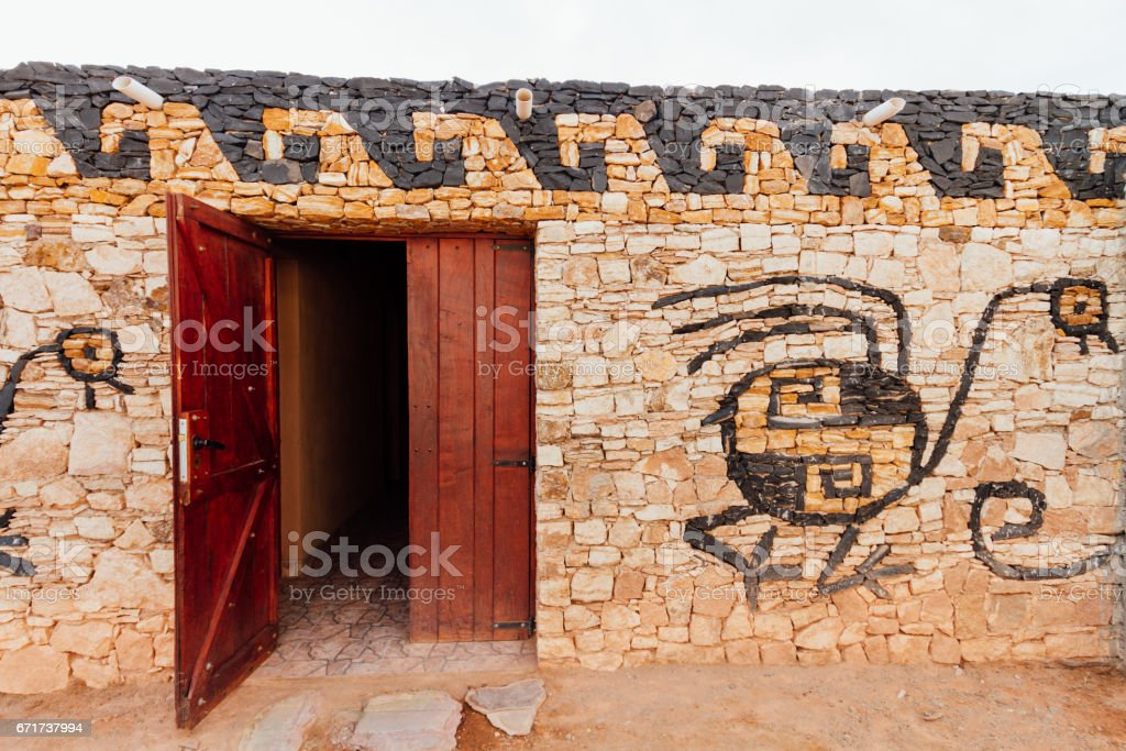 Wall of stone house with drawing of Suri in Catamarca stock photo