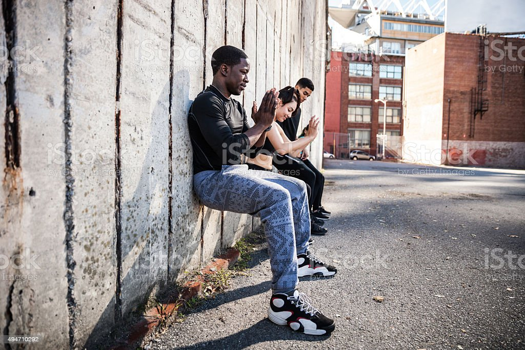 Wall sitting exercise urban outdoor gym in NYC stock photo