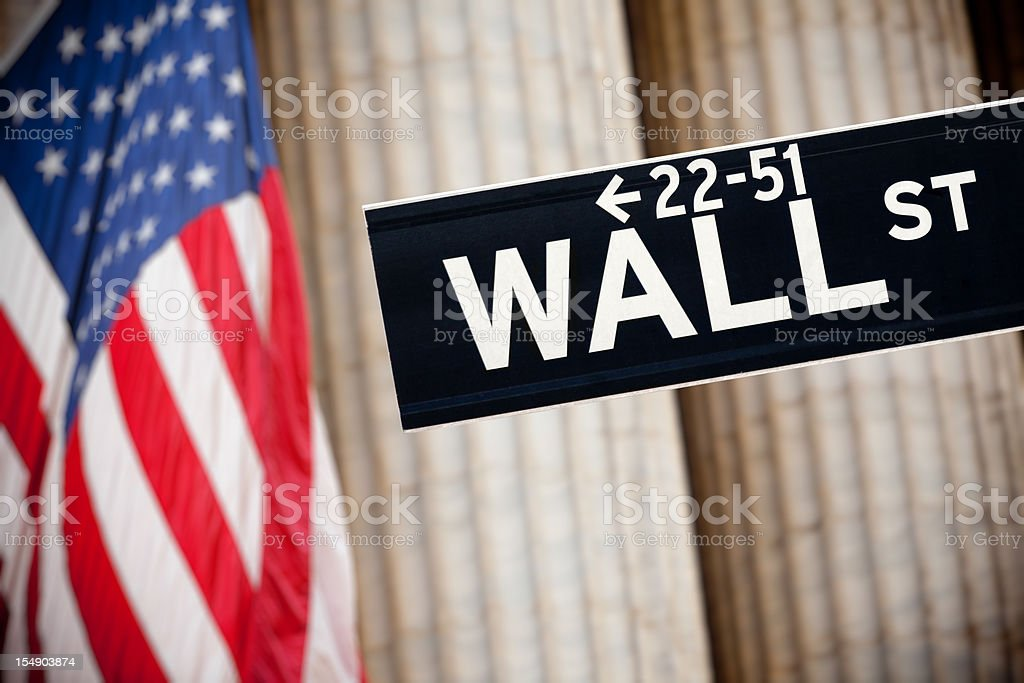 Wall street sign and American flag royalty-free stock photo
