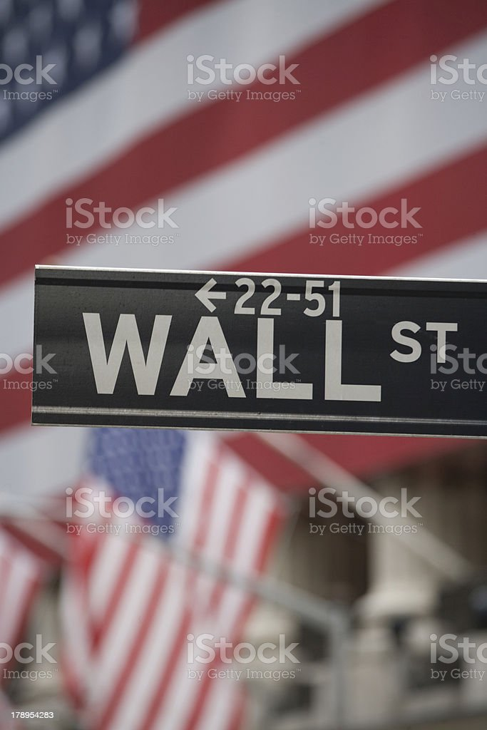 Wall Street Sign with American Flag in Background stock photo