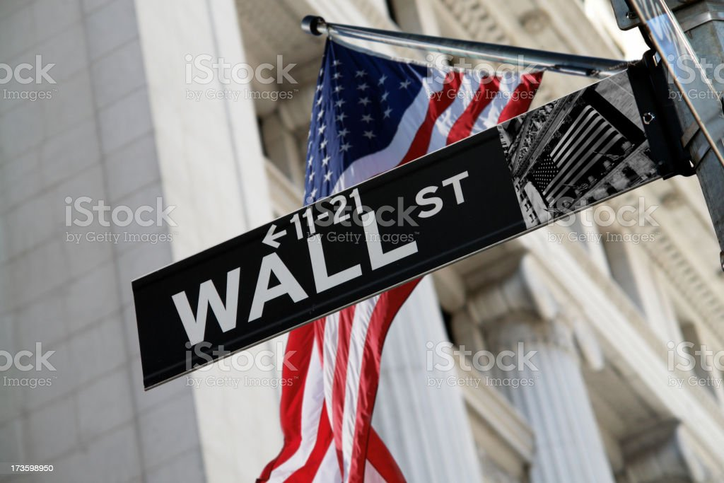 Wall Street Sign with US Flag Behind stock photo