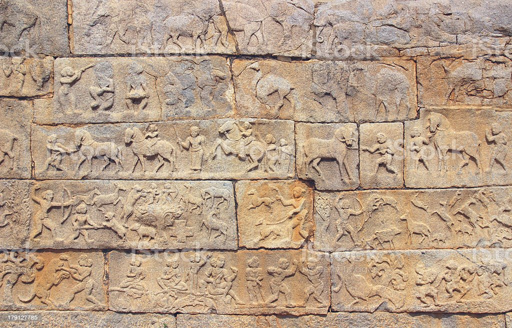 Wall with a carved relief: scenes of hunting and life royalty-free stock photo