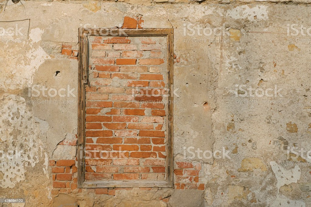 Wall with a window frame being bricked up stock photo