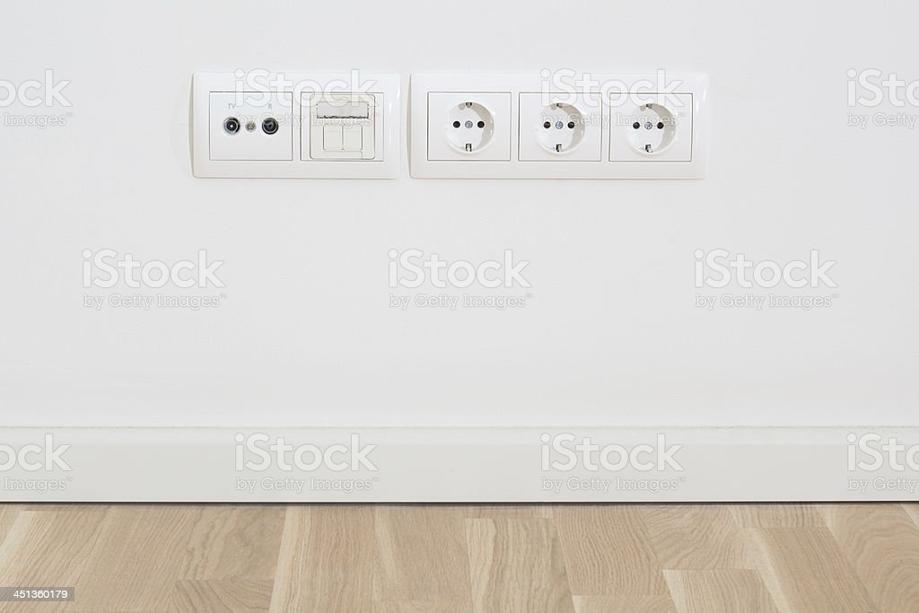 Wall with electric, TV, network plugs stock photo
