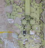 wall with flaking paint and old electric installation