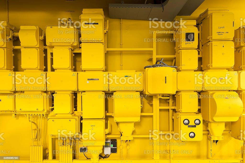 Wall with yellow switch-boxes supplying electricity in an office building stock photo