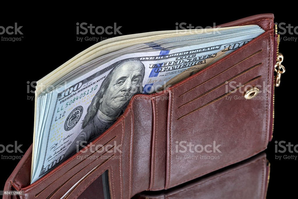 Wallet with a pack of dollars on black stock photo