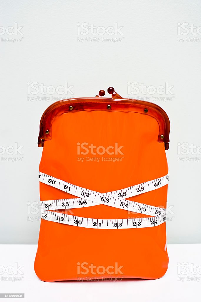 Wallet wrapped in tape measure showing a financial diet stock photo