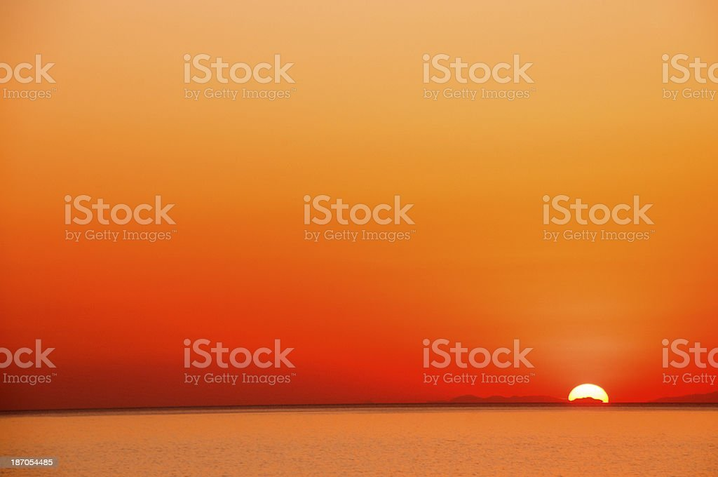 Wallpaper of Sun setting beyond water in orange skyline stock photo