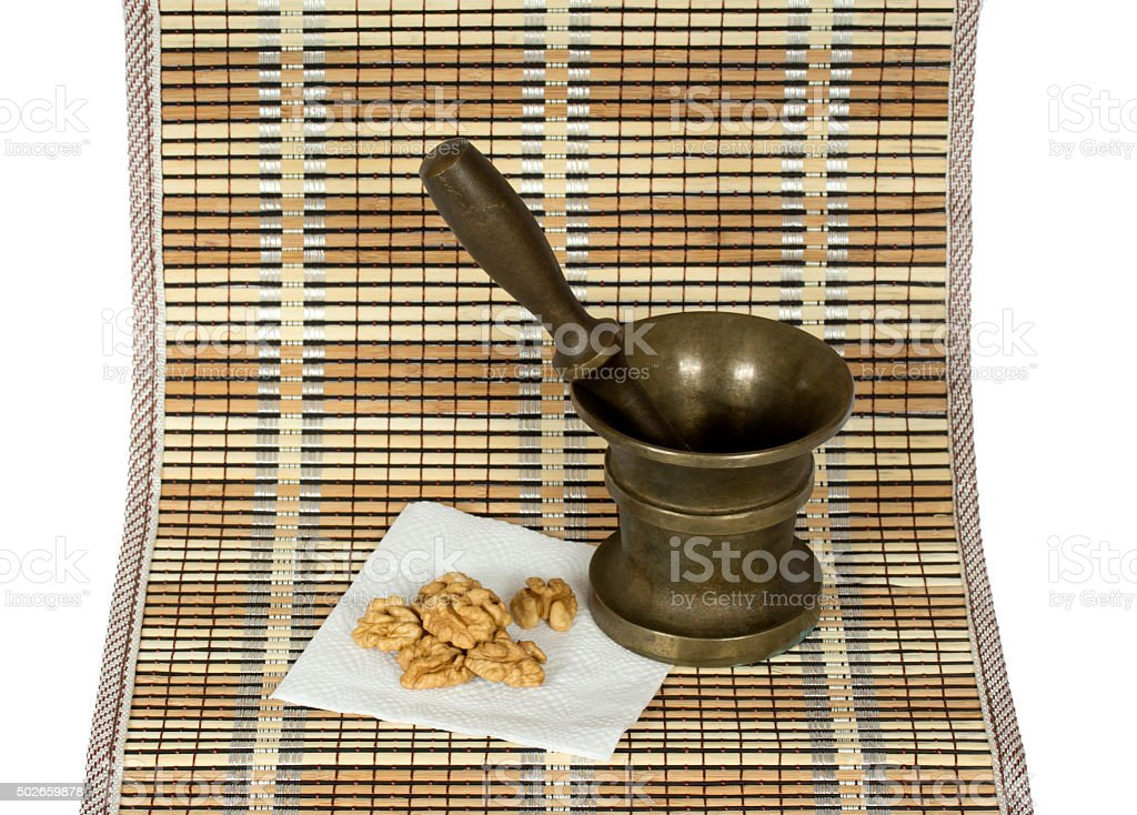 Walnut and the copper pounder (mortar) on the matting stock photo