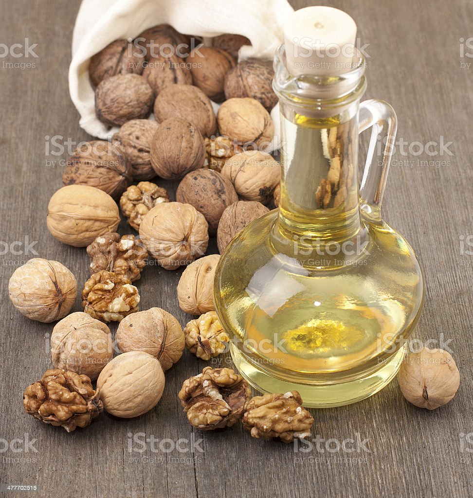 Walnut oil and walnuts on a wooden table. stock photo