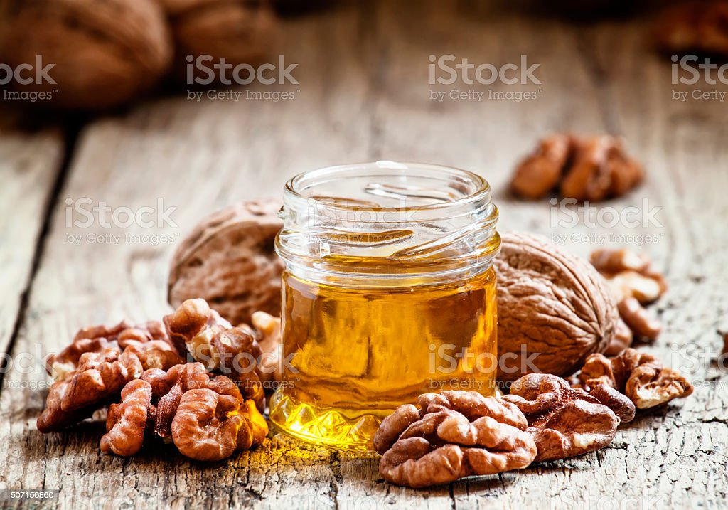 Walnut oil in a small jar and kernels stock photo