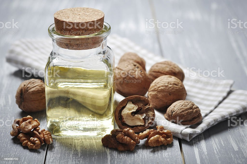 Walnut oil jar with nuts on wooden table stock photo
