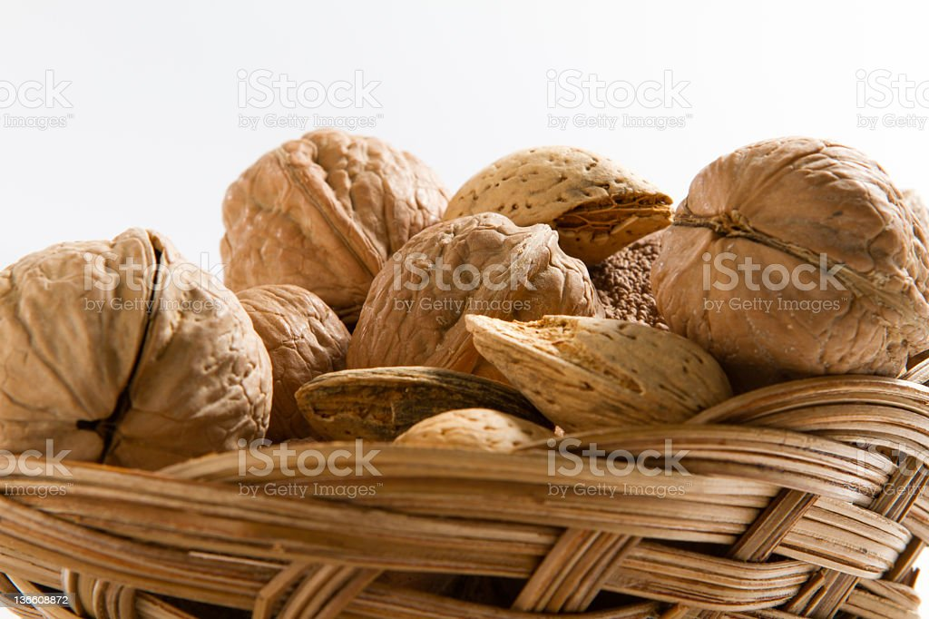 Walnuts and Almonds in their shells in a wicker basket stock photo