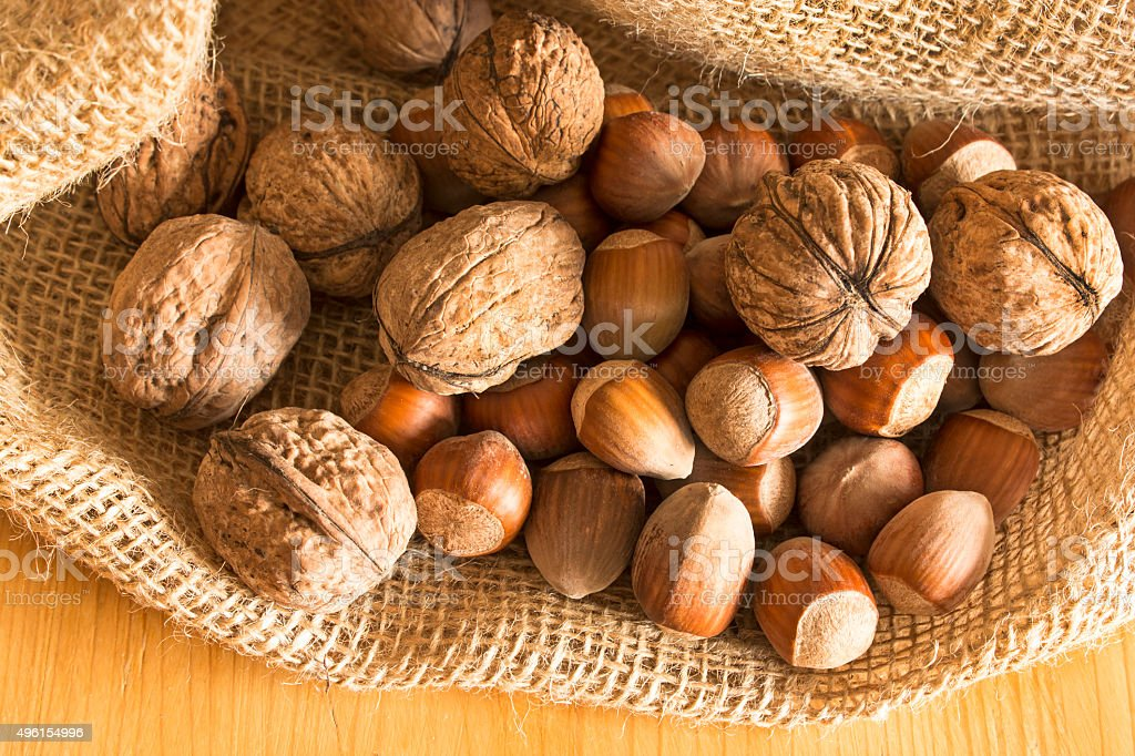 Walnuts and hazelnuts in a jute sack stock photo