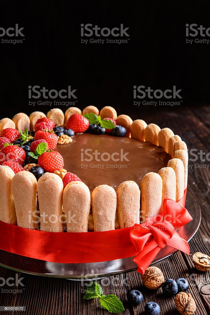 Walnuts cake with strawberries, blueberries and savoiardi biscuits stock photo