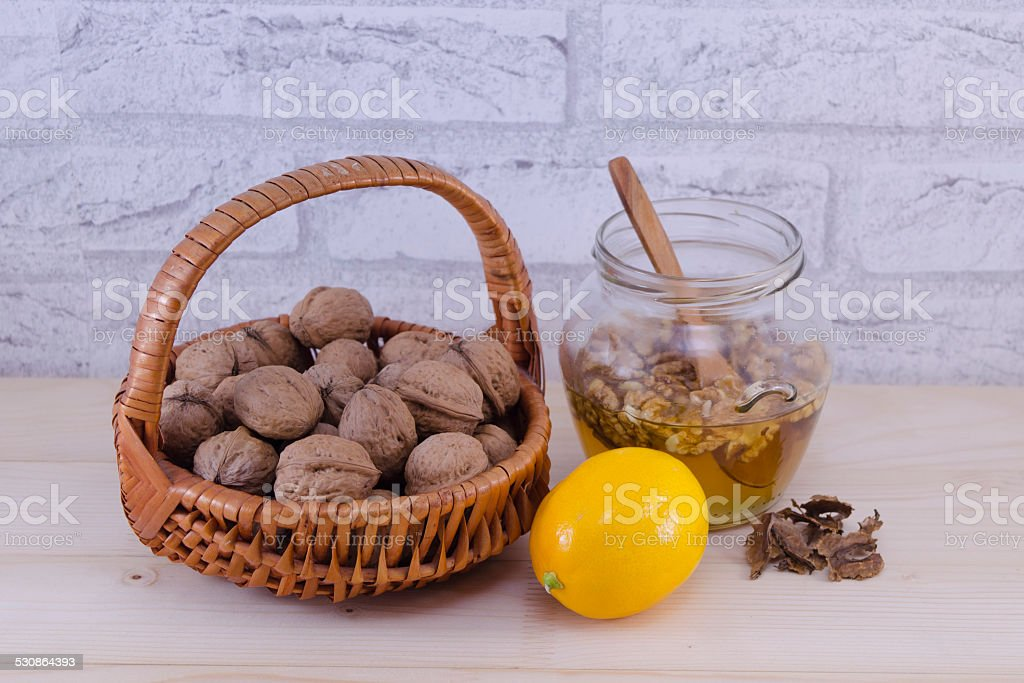 Walnuts in a jar of honey and a lemon stock photo