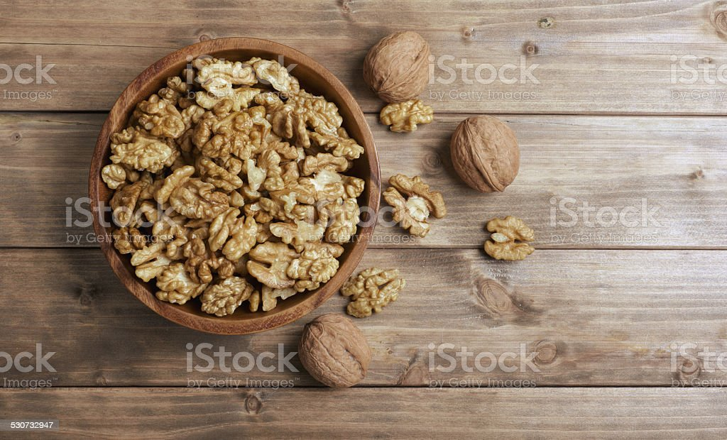 Walnuts in wooden bowl stock photo