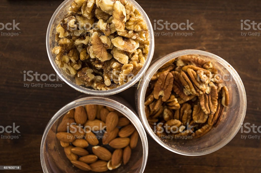 Walnuts, pecans, and almonds in containers stock photo