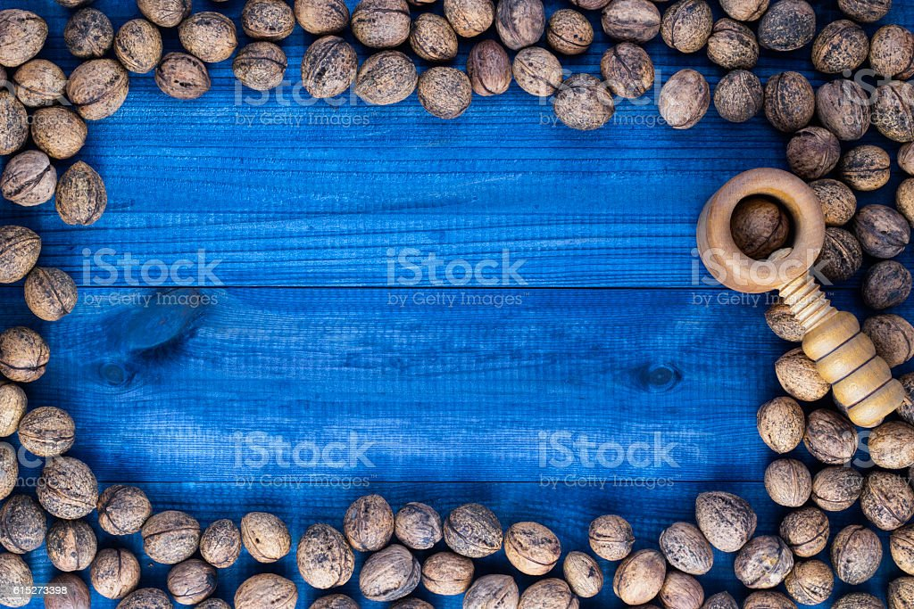 Walnuts with nutcracker on blue wooden table stock photo