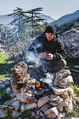 Wanderer cooking on bonfire, seating with hot cup of coffee.