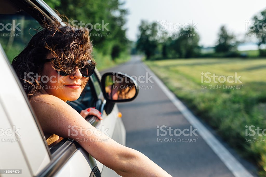 Wanderlust girl traveling by car in summer time stock photo