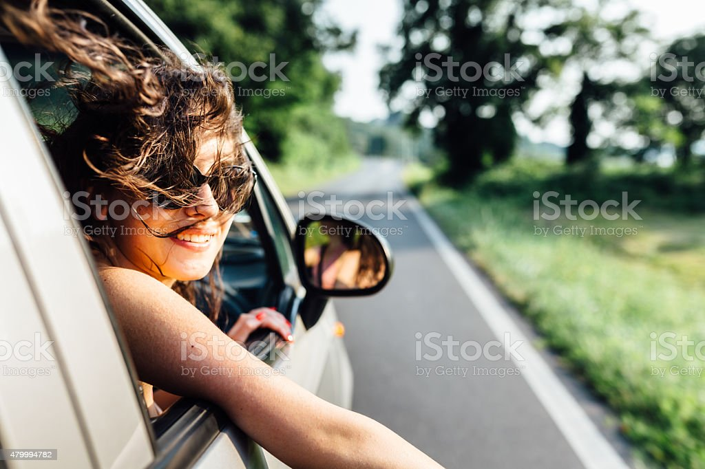 Wanderlust woman traveling by car in summer time stock photo