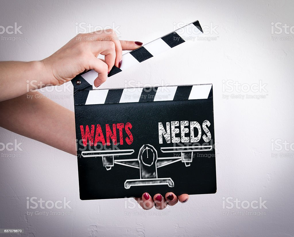 Wants and Needs Balance. Female hands holding movie clapper stock photo