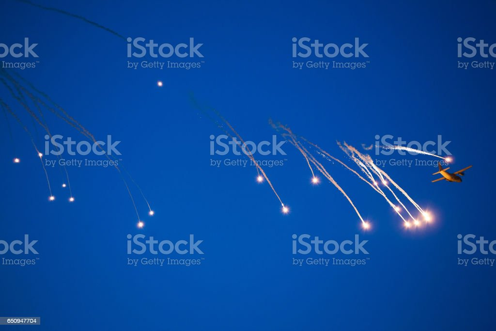 War plane dropping flares stock photo