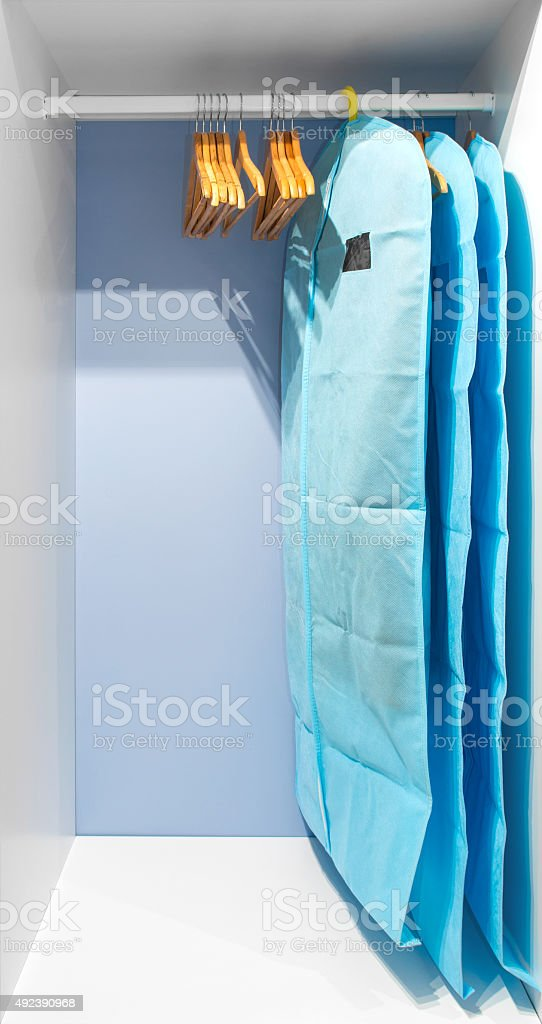 Wardrobe closet with clothes in cyan protective cover stock photo